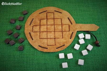 Queah-Spielfläche aus Leder mit Marmorsteinen schwarz und weiß.